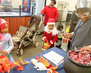 Michalene Hughley granbs candy for Kalia Anderson, 6 (left), and Nevaeh Shouse, 4, and at the Covelli Centre on Saturday afternoon. Quander Shouse, 2, is dressed as batman, and Nevaeh and Quander's mother Lavertta Shouse is pushing the stroller.