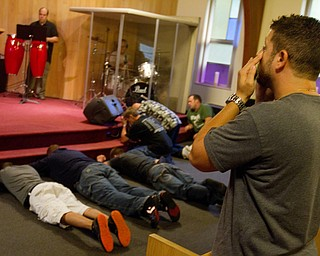 Geoffrey Hauschild|The Vindcator.8.24.2010.Pastor Bob Pavlich prays as OVTC members and other church attendees lie down in prayer during the group's weekly Wednesday night church service at Youngstown Christian Assembly.