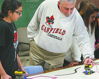 Salsis Salama has her teacher, Dave Izzo, check her robot in class Tuesday. Izzo recently received a grant to replace the old robotics equipment for two of his seventh-grade technology classes at Canfield Village Middle School.