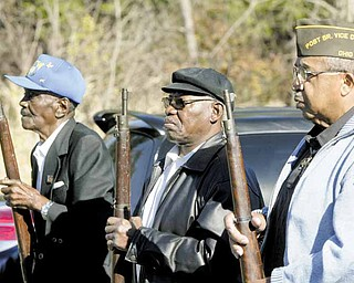 VFW Donald Lockett Post 6488 firing squad stands at order arms after firing a salute during Thursday's Veterans Day program at the post in Youngstown. From left are Jesse Duke, Ronell Carter and Lacy Hill.