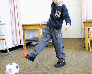 "Nicholai ""Kolya"" Denykin, 11, of the Renewal Orphanage in Dimitrov, Russia, practices his soccer kicking technique as part of his physical therapy at Youngstown Orthopaedic Associates in Canfield. Kolya, who was born with no legs beyond the knees, was fitted with prosthetics by Craig Svader of Advanced Anatomical Design in Girard and Canfield."