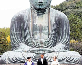 President Barack Obama visits the Great Buddha of Kamakura with Michiko Sato, temple director, and Takao Sato, the 15th chief monk of the temple, at Kotokuin Temple in Kamakura, Japan,  Sunday, Nov. 14, 2010. (AP Photo/Charles Dharapak)