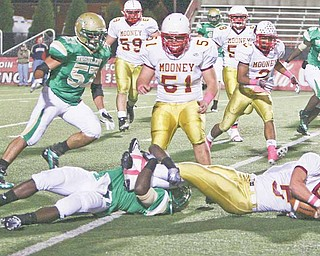 Ursuline High senior Mike Zappa (57) comes into help on a play during the Irish's victory over Cardinal Mooney this season. Zappa has been a backup player for Ursuline until this season, and is one of the team's mainstays on the off ensive and defensive lines.