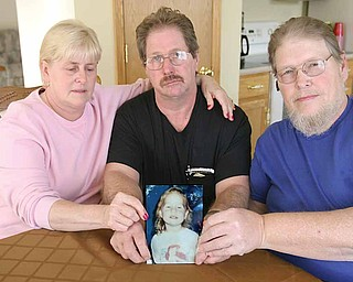 Family members of Jessica Ballew hold a portrait of her. They are, from left, Connie Ressler, Jessica's aunt; Virgil Ballew, her father; and Steve Ballew, her uncle. Gov. Ted Strickland's clemency to the killer of Jessica has angered the family.