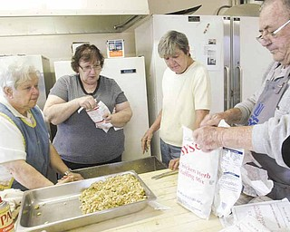 Judy Elliott, left, coordinator of the 30th annual Thanksgiving dinner at First Presbyterian Church in Youngstown, oversees the preparation of stuffing for the event. Continuing from left are members of the kitchen crew, Sandy Benson, Ellen McMichael and Al Shakley.