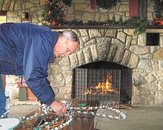 Jay Groner, Columbiana city service director, attaches lights to decorations in the main pavilion in Firestone Park. His work was in preparation for Christmas in Columbiana, which begins tonight.