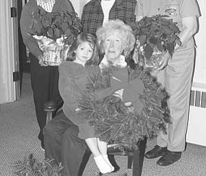 Nick Mays | Special to The Vindicator: Displaying a few of the live poinsettias, wreaths and swags to be sold as a benefit for the programs and services of the Children's Aid Society of Mercer County are, standing, from left, Kate Snyder, Helen Louise Donner and Joan Foster, and, seated, Julie Anhalt, who holds Layne Murphy, 3.