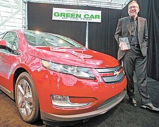 Joel Ewanick, General Motors Co. vice president for U.S. Marketing, holds the award won by the Chevy Volt as 2011 Green Car of the Year, presented by Green Car Journal, at the L.A. Auto Show Thursday, Nov. 18, 2010.