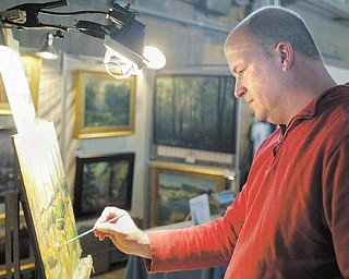 Canfield artist Chris Leeper works on a painting during annual Holiday  Open studio and Art Sale  in the Ward Bakery Building Sunday.
