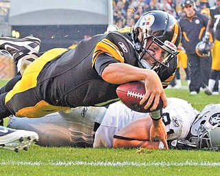 Pittsburgh Steelers quarterback Ben Roethlisberger, top, dives into the end zone over Oakland Raiders' Trevor Scott for a second-quarter touchdown during an NFL football game in Pittsburgh, Sunday, Nov. 21, 2010. (AP Photo/Gene J. Puskar)
