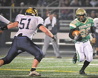 Ursuline's Akise Teague runs the ball against Kirtland during the first half of their game in Auora on Saturday night.