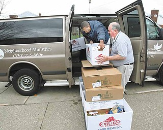 Former Neighborhood Ministries director David Stone and volunteer Walter Fowler, inside the van, have been boxing and delivering food for more than 30 years at Neighborhood Ministries. They were getting ready Monday to deliver food from the Campbell location to two other agency locations in Youngstown.