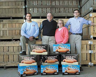 Vick Family Farms in Wilson, N.C. From left: Dwayne Ferrell, packing house manager, owner Jerome Vick and his wife Diane, and food safety manager Shea Leatherman pose in front of crates full of sweet potatoes.