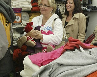William D. Lewis|The Vindicator  Debbie Kempers of Poland, left, and Rochelle Morelli of North Jckson wait in the check outline at Boardman Old Navy store about 5:30 am. The store opened at midnite.