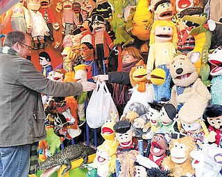 A vendor sells puppets at the Union Square Holiday Market, Sunday, Nov. 28, 2010 in New York.