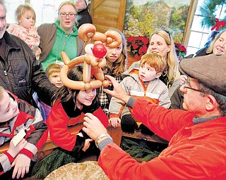 Balloon artist Joe Sullivan, above,  presents Lily Vari-Coppola, 6, of Lowellville with a Rudolph the Red-Nosed Reindeer balloon hat at Lanterman's Mill on Sunday.  The annual Olde-Fashioned Christmas at Lanterman's Mill drew thousands of area residents Saturday and Sunday.