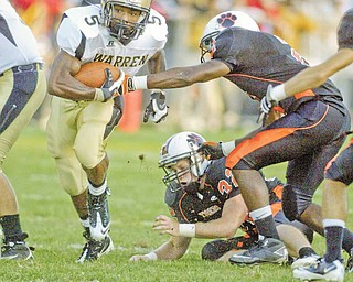 Harding's Demond Hymes gets past Howland's Tony Osborne and Dan Russell during first quarter action Friday at Howland.