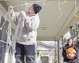 Mark Cole and his wife Darlene took advantage of Monday's good weather to begin decorating for the holiday season. Mark kept busy stringing lights off the front porch of the couple's Midlothian Boulevard home in Youngstown while Darlene removed pumpkins and other fall decorations.