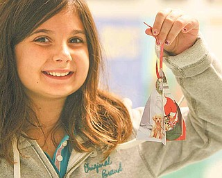 Poland North Elementary fourth-grader Sophi Gawdyda shows off her ornament made out of old holiday cards. The Mahoning County Green Team helped students make a variety of recycled ornaments Tuesday.