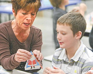 De De Smith of the parent-teacher organization lends some helping hands to Austin Tusinac as he finished his tree ornament.