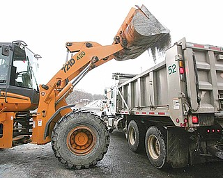 Workers move road salt from a bin to a truck at the Mahoning County Engineer's Office on Industrial Road.