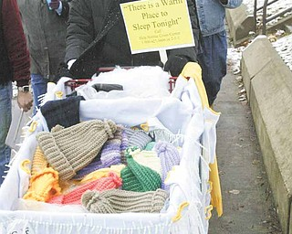 Participants in the third annual Homeless Walk make their way along Martin Luther King Jr. Boulevard in Youngstown. Cindy Pickens from Help Hotline Crisis Center pushed a shopping cart filled with knitted mittens and hats.