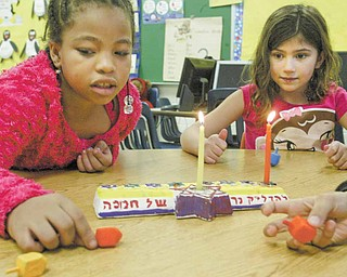 Sapphire Cathey, left, and Millie Heschmeyer, first-graders at Akiva Academy in Youngstown, spin dreidels, the Yiddish word for tops. Dreidels are part of the fun at Hanukkah, which began at sundown Wednesday. The eight-day festival continues until sundown next Thursday.