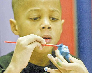 Bronx Teague, a first-grader at Akiva Academy, concentrates on painting a candle holder for a menorah. The students were learning about Hanukkah traditions, which include lighting candles on a menorah.