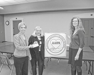 Research rewarded: An educational program on research was presented at a recent Alzheimer's Assistance and Referral Network meeting at Boardman Public Library by Mary Ann Oakley, education and information core coordinator, and Beth Sarles, clinical core staff, from the University of Pittsburgh Alzheimer's Disease Research Center. At the close of their program a check for $4,500 to further study at the research center is presented by Dorothy Barto, network director, to Oakley, left, as Sarles watches.