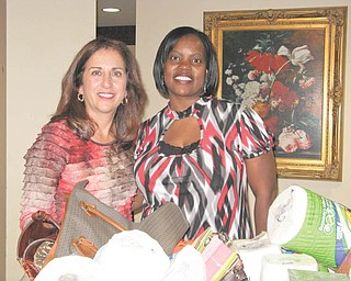 A good deed is done: Sperry Rongone, left, a Boardman-Poland Junior Women's League provisional member, and Audrey Walker from the Sojourner House stand with some of the items collected for Sojourner. The house shelters women and children who are victims of domestic violence. Rongone's provisional project was to collect items from members of the BPJWL that were included on a wish list from residents. She will be installed as a new member at the December social.