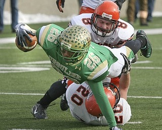During the second quarter, Ursuline's Akise Teague pushes past Coldwater's #20 Drew Feltz and #8 Ross Wermert to score another touchdown. The Ursuline Irish have achieved their primary season goal: to win the state title for a record third-straight time. The Fighting Irish had an impressive end to their season with a 51-21 victory over Coldwater in the Division V State Championship game at Canton's Fawcett Stadium Saturday, Dec. 4, 2010.