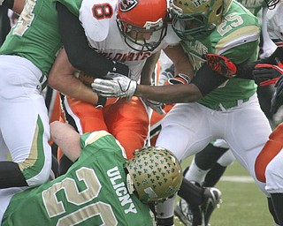 Coldwater's #8 Ross Wermert is surrounded by Ursuline's #20 Craig Ulicny and #24 (far left)  Jermaine Williams. The Ursuline Irish have achieved their primary season goal: to win the state title for a record third-straight time. The Fighting Irish had an impressive end to their season with a 51-21 victory over Coldwater in the Division V State Championship game at Canton Fawcett Stadium Saturday, Dec. 4, 2010.
