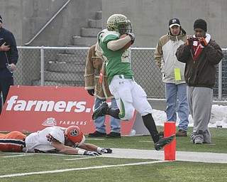 Hopping into the end zone, Ursuline's Akise Teague leaves Coldwater's #21 Reese Klenke face down on the turf. The Ursuline Irish have achieved their primary season goal: to win the state title for a record third-straight time. The Fighting Irish had an impressive end to their season with a 51-21 victory over Coldwater in the Division V State Championship game at Canton's Fawcett Stadium Saturday, Dec. 4, 2010.