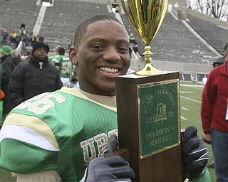 Mr. Football, Ursuline's Akise Teague, marches the championship trophy around the stadium after winning the state title. The Ursuline Irish achieved their primary season goal: to win the state title for a record third-straight time. The Fighting Irish had an impressive end to their season with a 51-21 victory over Coldwater in the Division V State Championship game at Canton's Fawcett Stadium Saturday, Dec. 4, 2010.