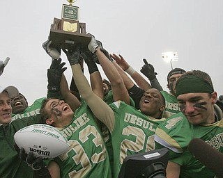 RAISING IT HIGH -  Ursuline's #33  Jeff Podolsky and  #26 Akise Teague  hoist the championship trophy. The Ursuline Irish achieved their primary season goal: to win the state title for a record third-straight time. The Fighting Irish had an impressive end to their season with a 51-21 victory over Coldwater in the Division V State Championship game at Canton's Fawcett Stadium Saturday, Dec. 4, 2010.