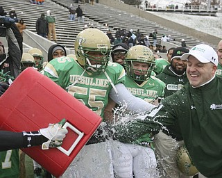 Ursuline Head Coach Dan Reardon dodges water, as #55 Ronald Green and #20 Craig Ulicny  look on. The Ursuline Irish achieved their primary season goal: to win the state title for a record third-straight time. The Fighting Irish had an impressive end to their season with a 51-21 victory over Coldwater in the Division V State Championship game at Canton's Fawcett Stadium Saturday, Dec. 4, 2010.