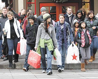 Shoppers carry their bags as they walk in downtown Seattle on Nov. 26, 2010. The service sector expanded for the 11th straight month in November and at the fastest pace in six months.
