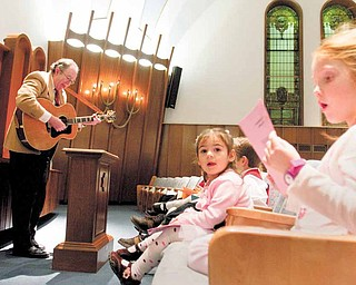 Lily Weiss (right), 6, of Canfield, and Saadyiah Leff (second from right), 2, of Cortland, sing Hanukkah themed songs as Rabbi Franklin Muller plays guitar during a Hanukkah celebration at Rodef Sholom in Youngstown on Sunday evening.