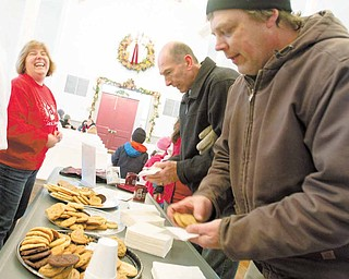 Boardman PTA Council President, Cheryl Dutko, enjoys a laugh as Boardman residents, Ron Mistovich and Dave Erck, grab cookies and hot chocolate during the 14th Annual Boardman Community Christmas at Boardman Township Park on Sunday afternoon..
