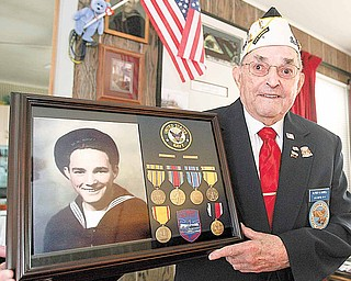 "Alfred ""Al"" Gaskell of Howland, a member of the Pearl Harbor Survivors Association Mahoning Chapter 5, holds a display of the decorations he received from  his service in the Navy in World War II. Included is a picture of himself in his Navy uniform from 1941."