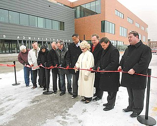 From left, dignitaries cutting the ribbon Monday to open the northward Hazel Street extension connecting Youngstown's downtown to Youngstown State University outside the university's Williamson College of Business are: Councilman John R. Swierz, D-7th; Jason Riffle, president of United Civil Contractors and Developers Inc. of Hubbard, which built the street; Councilwoman Annie Gillam, D-1st; State Sen. Joe Schiavoni, D-33rd, of Canfield; State Rep. F. Hagan, D-60th, of Youngstown; Mayor Jay Williams; Cynthia Anderson, YSU president; State Rep. Ronald V. Gerberry, D-59th, of Austintown; David Mosure, vice president of MS Consultants of Youngstown, project engineers; and Charles Shasho, the city's deputy director of public works.