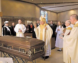 Bishop George V. Murry of the Diocese of Youngstown, center, blesses  Monsignor Thomas F. Kelly during a Mass of Christian burial Monday morning at St. Christine Church in Youngstown. Monsignor Kelly, who died Nov. 30, was pastor emeritus of the church.
