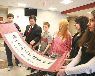 Deng Zhongqing, an educator from China, second from left, shows Girard Junior/Senior High School students a friendship scroll that he brought as a gift. Deng is being hosted by Louise Mason, junior high principal, who will visit China in the spring. Seventh-graders are, from left, Ben Norman, Nick Walker, Destiny Brenna, Alexis Leedy and Lea Buonavola