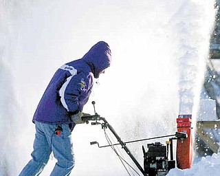 Kevin Eastvold of Mason City, Iowa, pushes through the snow at the end of his driveway with a snowblower on Sunday, Dec. 12, 2010. Winter storms passed over North Iowa over the weekend, dumping several inches of snow over the region and causing numerous accidents.