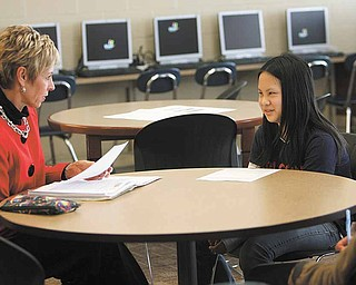 Patte Ulery, left, reads over a fable with Wendy Liu, a sixth-grader at Austintown Middle School. Wendy will be exiting the English tutoring program this year. She grew up in China.