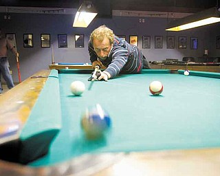 Earl Strickland, former world-champion pool player, practices at the Ice Breakers pool hall behind the Ice House Inn in Austintown. Strickland, of Greenboro, N.C., was introduced to the bar's owner about 18 months ago and stops by to give lessons or exhibitions.