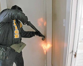 A shotgun blast blows the latch off a bedroom door as part of a tactical-entry training exercise by members of the Mahoning Valley Violent Crimes Task Force.