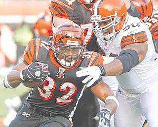 Cincinnati Bengals running back Cedric Benson (32) is tackled by Cleveland Browns defensive end Kenyon Coleman (90) in the first half of an NFL football game, Sunday, Dec. 19, 2010, in Cincinnati.