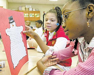 Taft Elementary School fourth graders Tanesha Bryant, left, and Tejhae Glenn look over letters they wrote to military personnel serving in Afghanistan. The letters were a writing project in teacher Laurie McEwans's class at the Youngstown school.