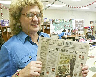 "Taft Elementary fourth-grade teacher Laurie McEwan holds the Nov. 7 edition of The Vindicator with the ""Operation Holiday Cheer"" feature that prompted the idea."